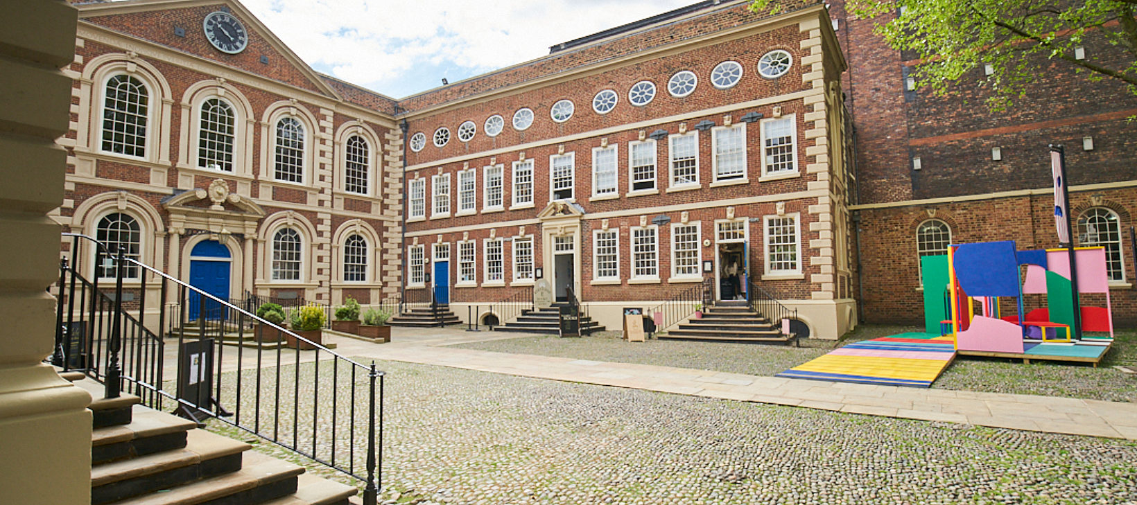 Image shows the Bluecoat building from the courtyard, with Bluecoat Platform, a colourful sculpture, in the right hand corner.