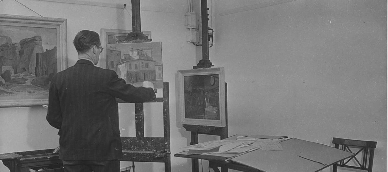 An artist stands with their back to the camera facing an easel. There are other paintings in the background and a table and chair in the room.