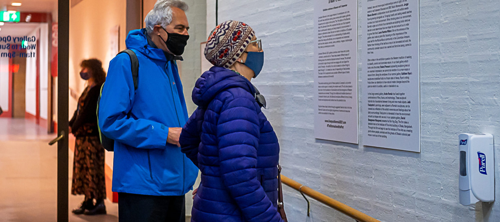 Two customers wearing masks reading Biennial introduction
