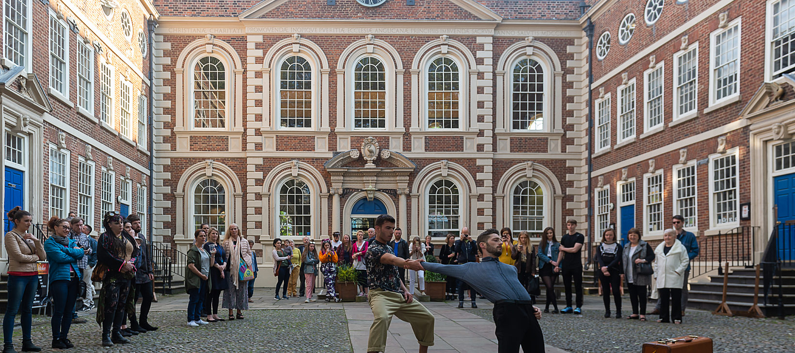 Two dancers perform in Bluecoat's courtyard with a packed audience behind them. In the background you can see the Bluecoat building.