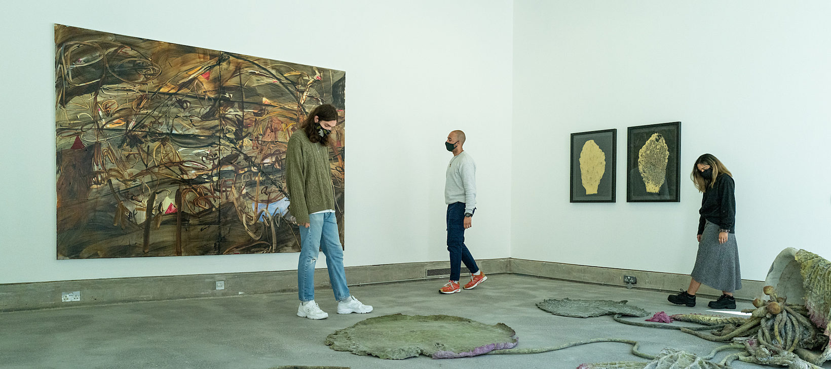Three people are walking around a gallery space with paintings on the wall and sculptures on the floor.