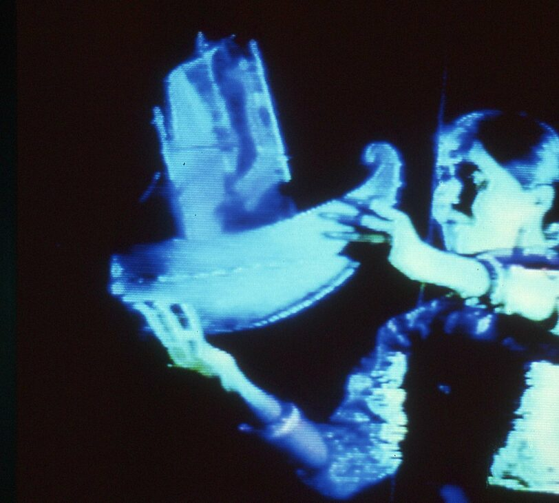 Images shoes a person holding a miniature sculpture of a boat, shrouded in blue light against a black background