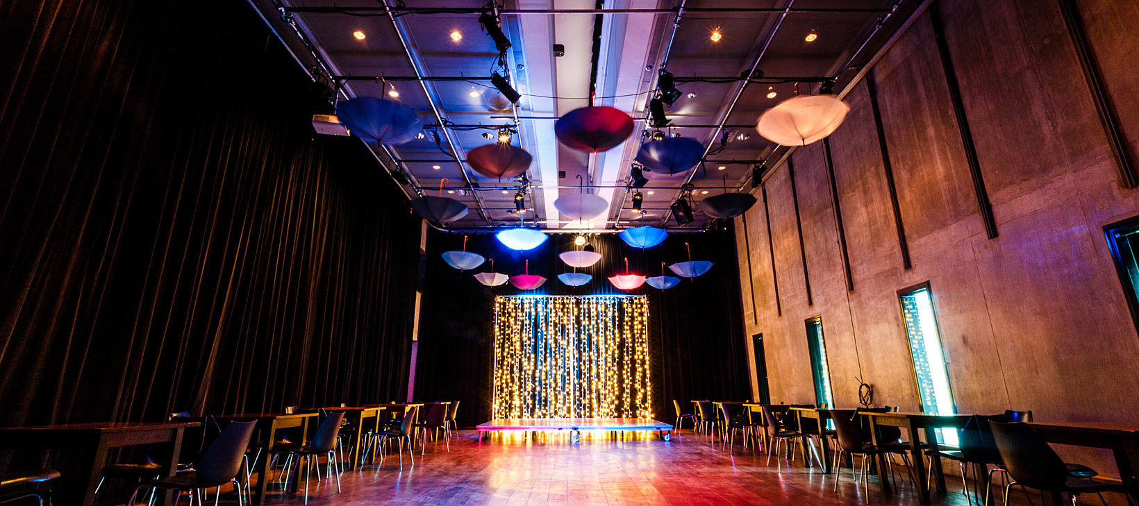A large room is dimly lit with chairs and tables on either side of the floor, multi coloured umbrellas hanging from the ceiling and a glittery platform stage is at the end of the room.